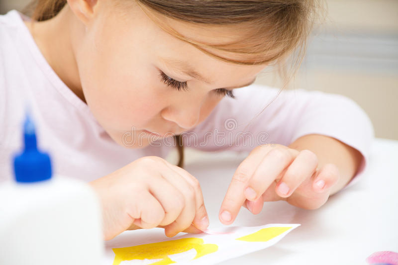 Little girl doing arts and crafts in preschool. Cute little girl applying a color paper using glue while doing arts and crafts in preschool royalty free stock image