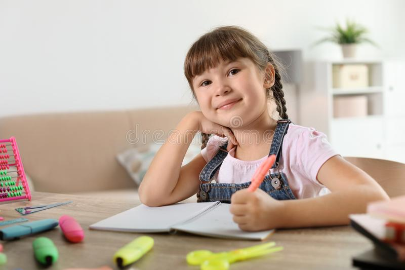 Little girl doing assignment at home stock photo