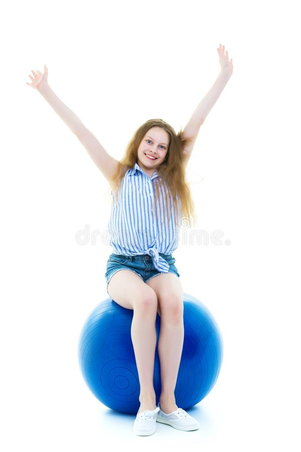 Little girl doing exercises on a big ball for fitness. royalty free stock image