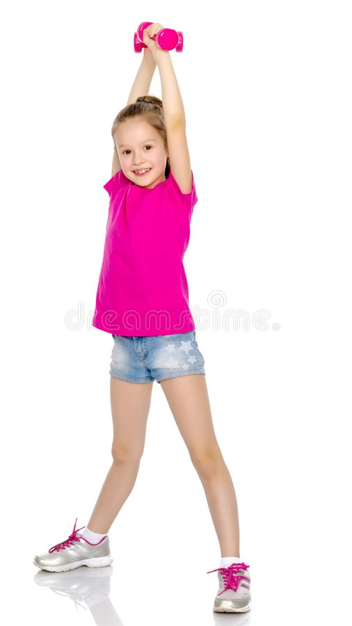 Little girl doing exercises with dumbbells. royalty free stock image