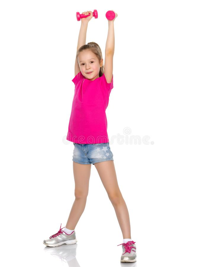 Little girl doing exercises with dumbbells. royalty free stock photography