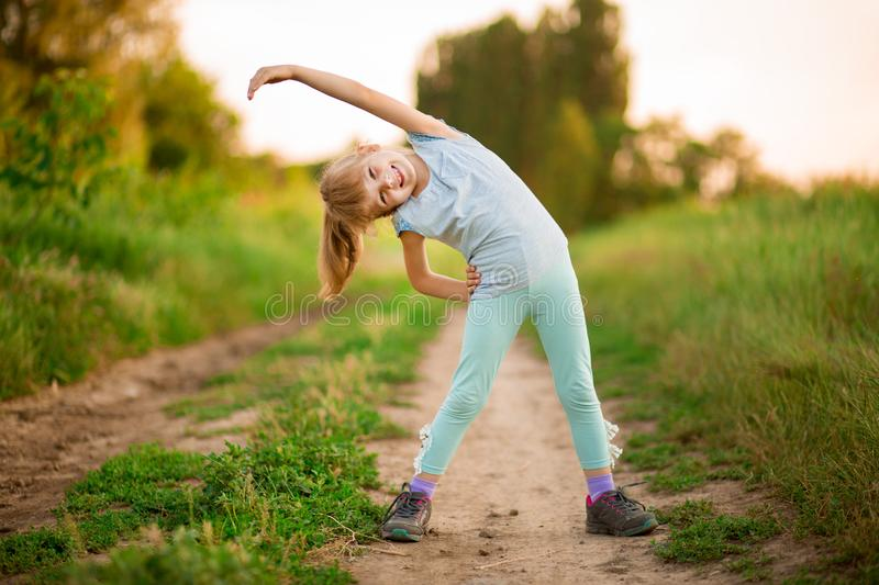 Little girl doing fitness exercises outdoor stock images