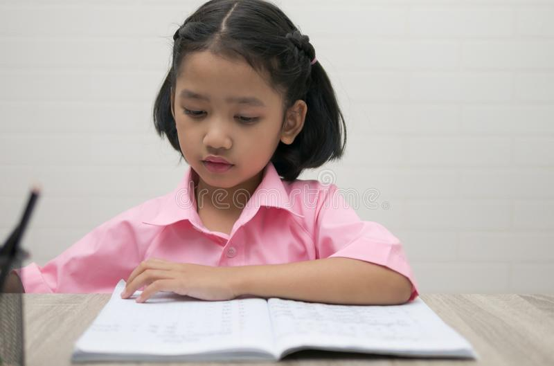 The little girl is doing homework stock photo