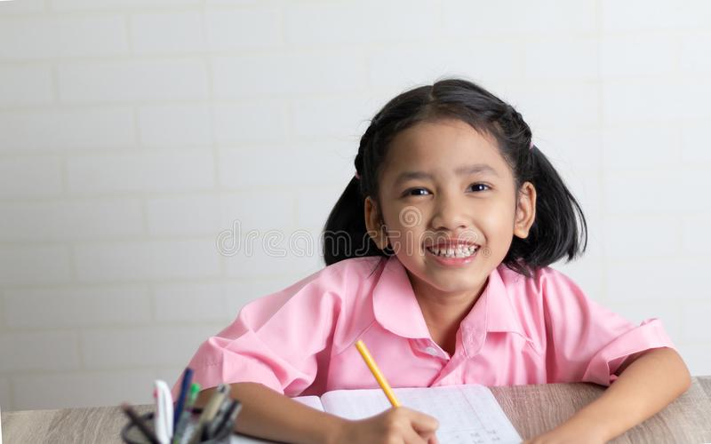 The little girl is doing homework happily and smile royalty free stock photography