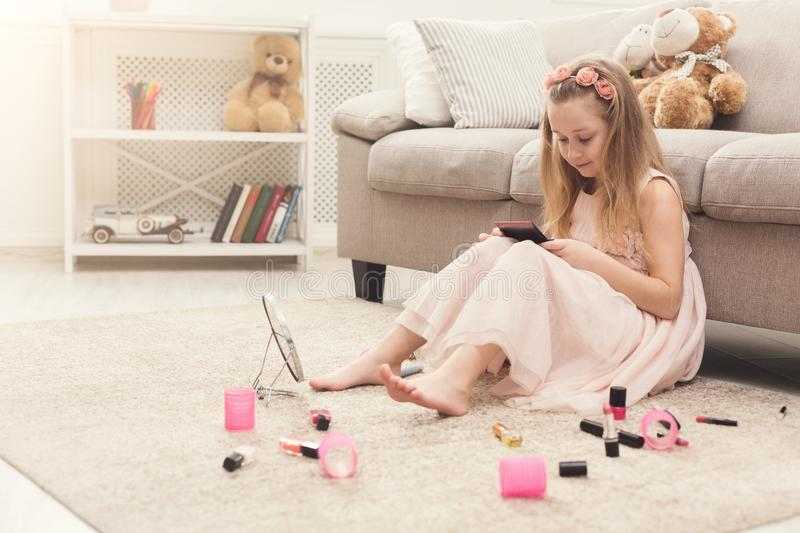 Little girl doing make up with mom`s cosmetics stock photography