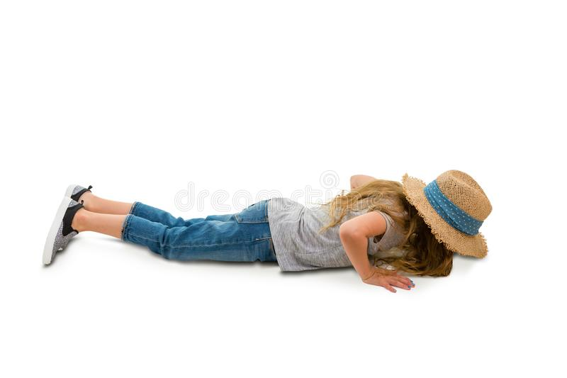 Little girl doing press-ups in side view. Fit little girl in jeans and a trendy straw hat doing press-ups in side view over a white background with copy space stock image