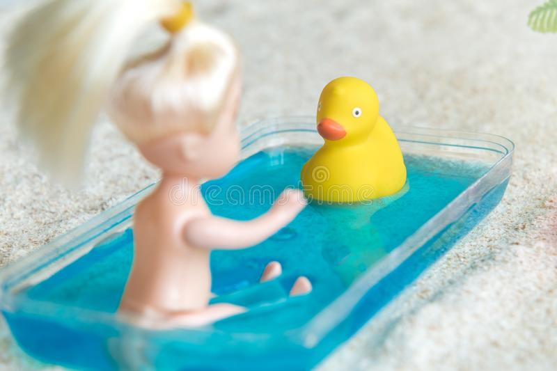 Little girl doll playing with yellow rubber duck in kiddie pool at the sandy beach tropical resort stock photo