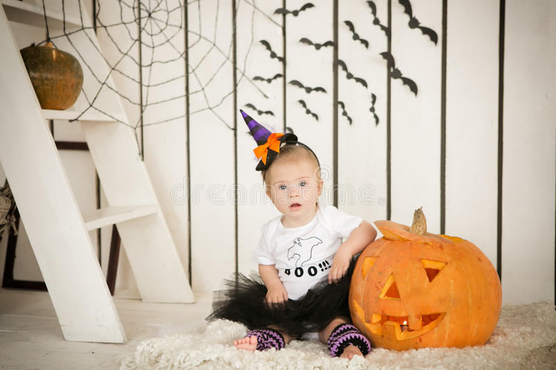 Little girl with Down Syndrome sitting with a broom near the big pumpkin royalty free stock photography