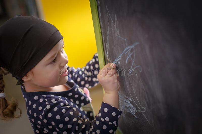 Little girl is drawing with blue chalk on a blackboard royalty free stock photography