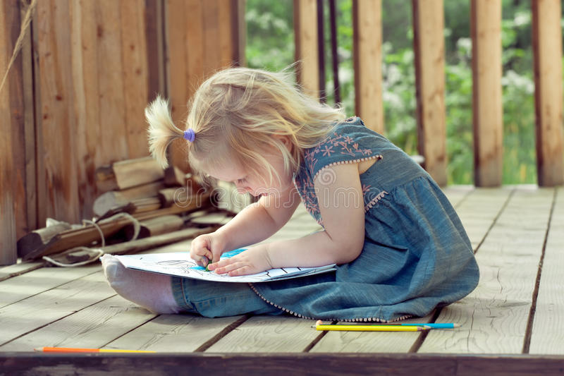 Little girl drawing with colored pencils on a country house wood stock image