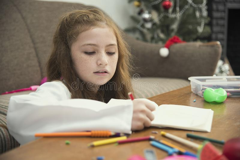Little girl drawing a colorful pictures using pencil crayons stock photography