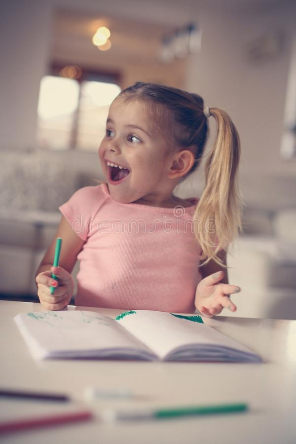 Little girl drawing and expressive positive emotion. Close up image. stock photography