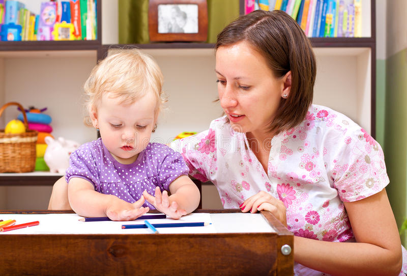Little girl drawing with her mother royalty free stock images