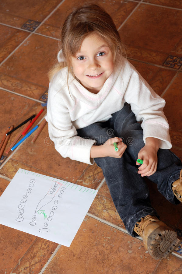 Little girl drawing a house. Little girl sitting on the floor and drawing a house stock images