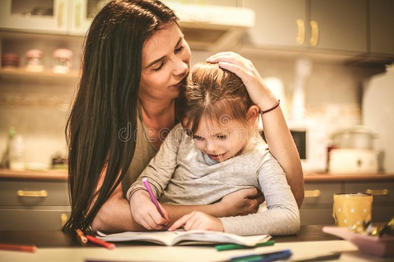 Little girl drawing with Mom. Close up. stock photos