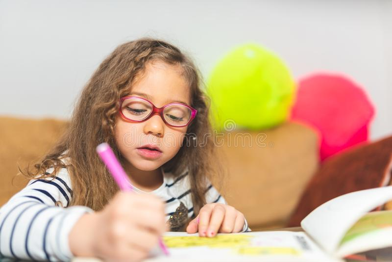 Little Girl Drawing on a Notebook royalty free stock photos