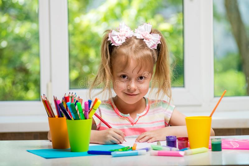 Little girl drawing paints and crayons to a room with a window. royalty free stock photo