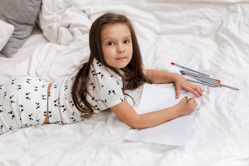 Little girl drawing pictures while lying on bed. stock photography