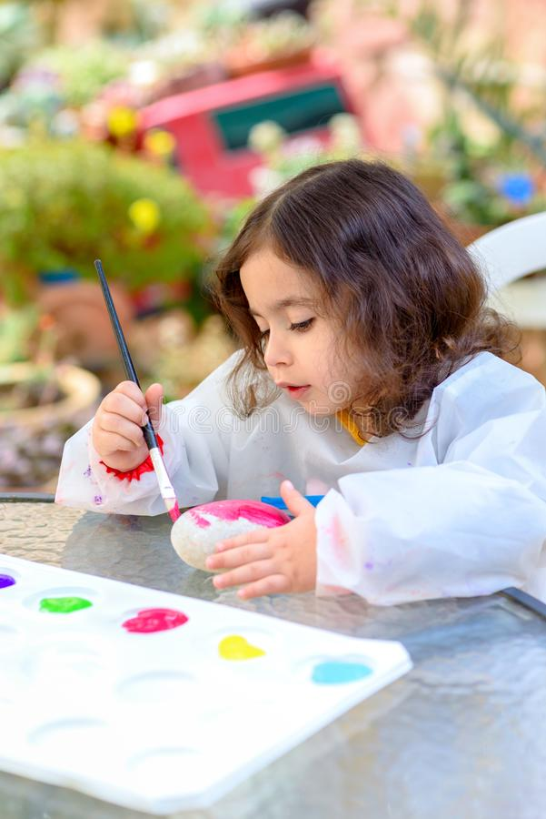Little Girl Drawing On Stone Outdoors In Summer Sunny Day. Portrait of little child painting, summer outdoor.Kid drawing on a stone royalty free stock image