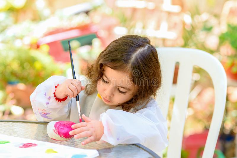 Little Girl Drawing On Stone Outdoors In Summer Sunny Day. Portrait of little child painting, summer outdoor.Kid drawing on a stone royalty free stock photography