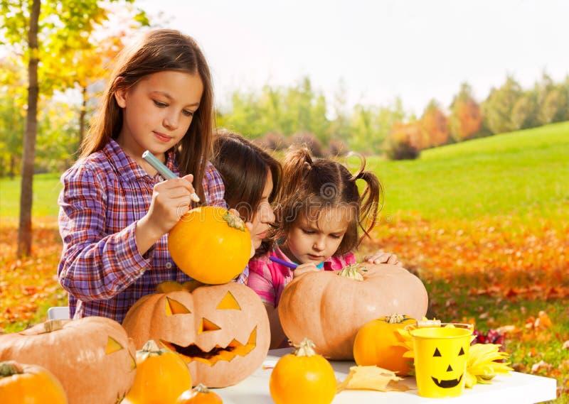 Little girl draws on Halloween pumpkin stock image