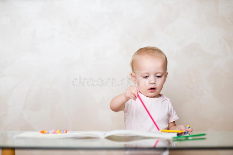 Little girl draws a line with a pink pencil in an album stock image
