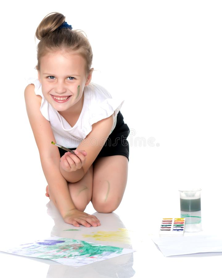 A little girl draws paints on her body royalty free stock photo