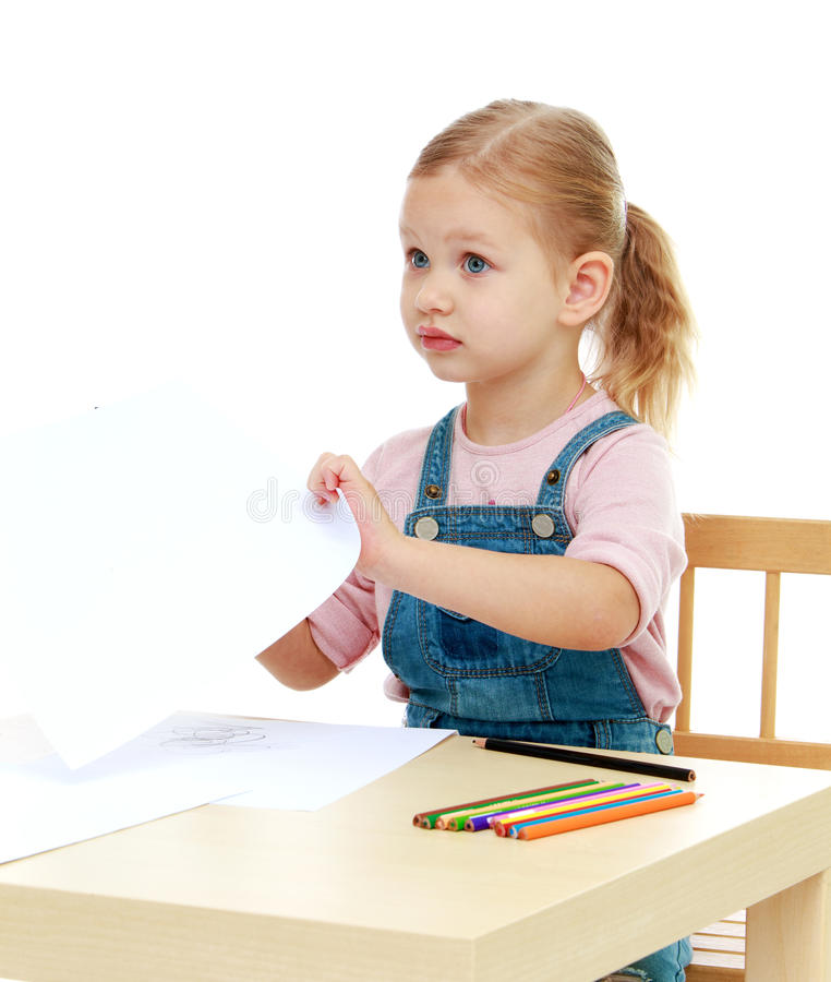 Little girl draws pencils sitting at the table. stock image