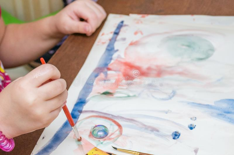 A little girl draws picture with paints and a brush royalty free stock photo