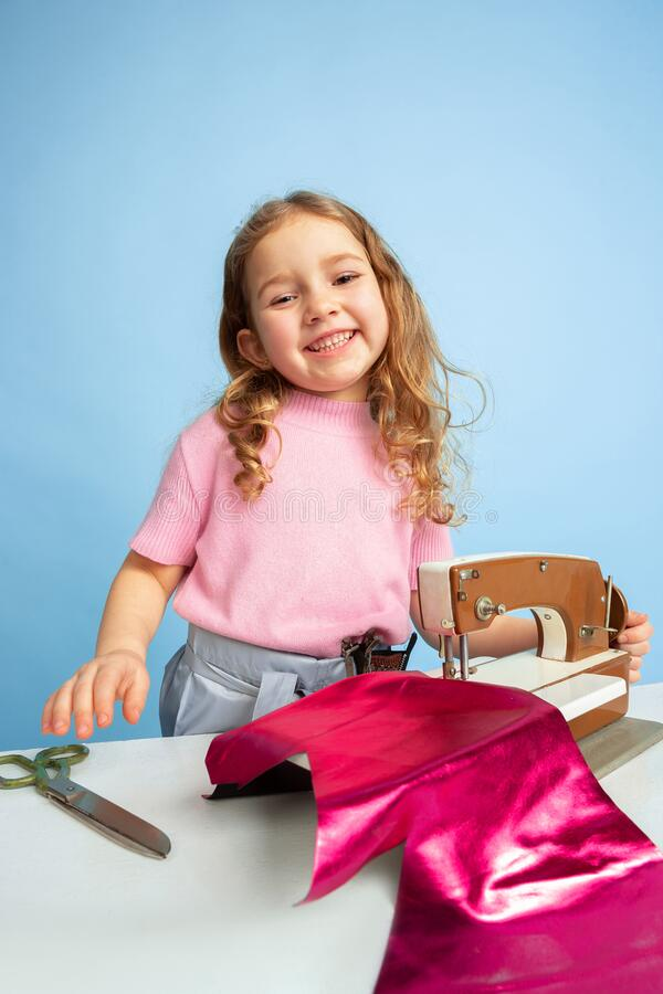 Little girl dreaming about future profession of seamstress royalty free stock images