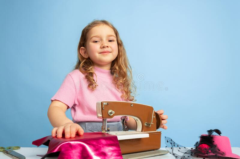 Little girl dreaming about future profession of seamstress royalty free stock photo