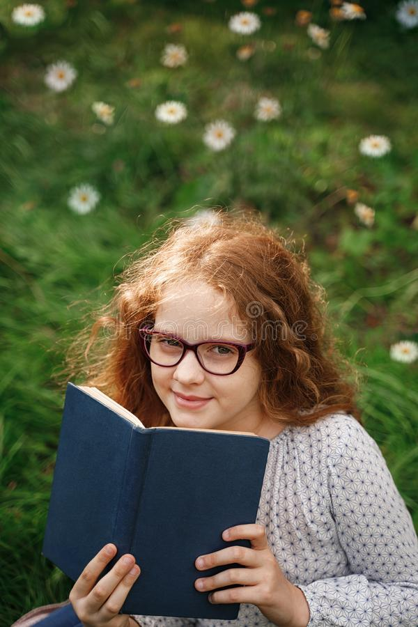 Little girl dreaming or reading a book in outdoors royalty free stock photos