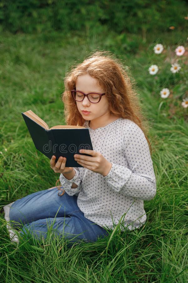 Little girl dreaming or reading a book in outdoors. royalty free stock photography