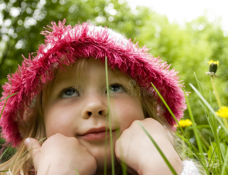 Little girl dreams in the grass stock images