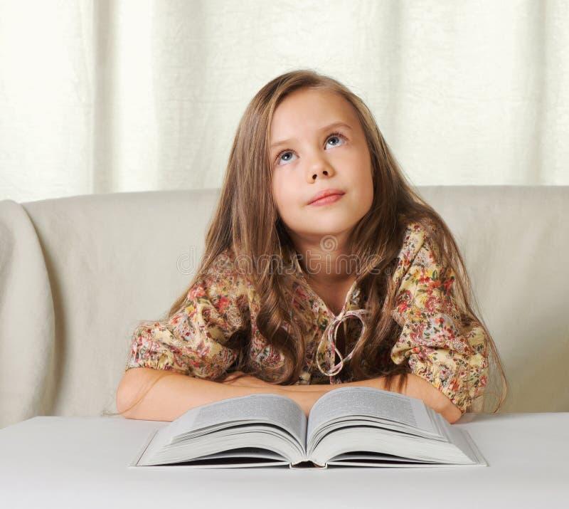 Little girl dreams when reading the book stock photo