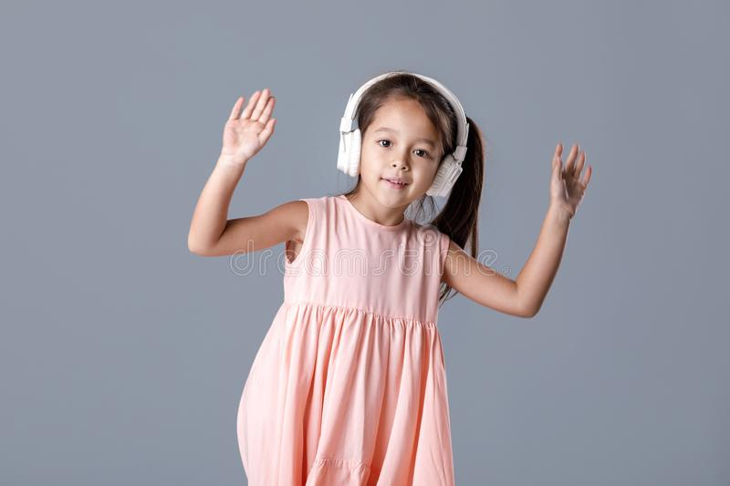 Little girl in dress and headphones listens to music and dances stock photos