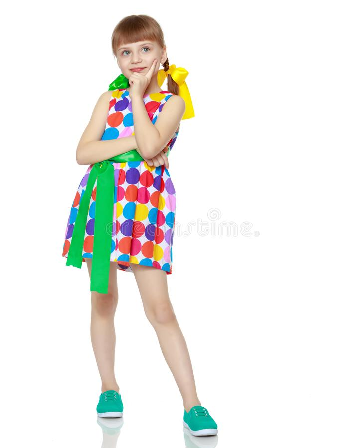A little girl in a dress with a pattern from multi-colored circl royalty free stock photos