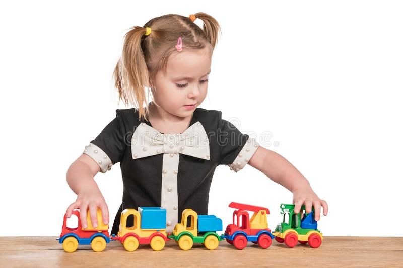 Girl playing with a car. Little girl in a dress playing toy cars on a wooden table isolated on a white background royalty free stock photography