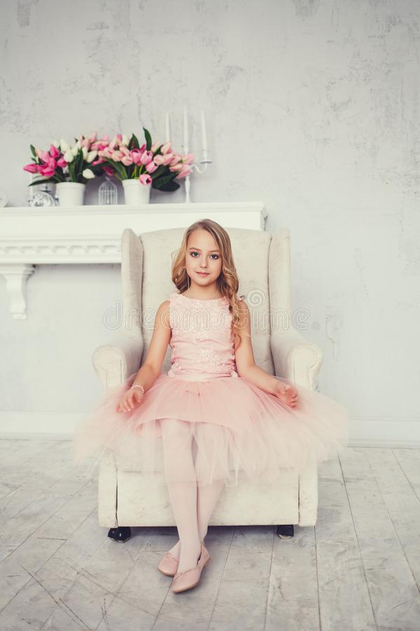 Little girl in a dress sits in a chair royalty free stock images