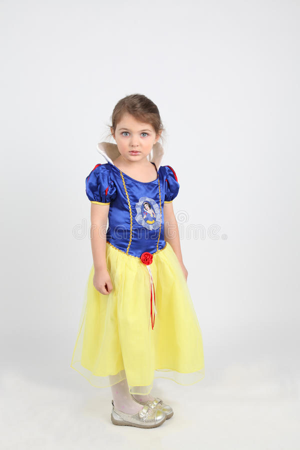 Little girl in dress of snow white. Photo of little girl in blue and yellow dress royalty free stock images