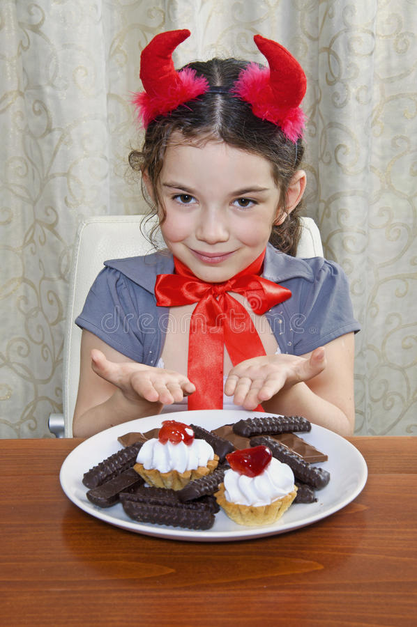 Little girl dressed as devil eats sweets at table stock images