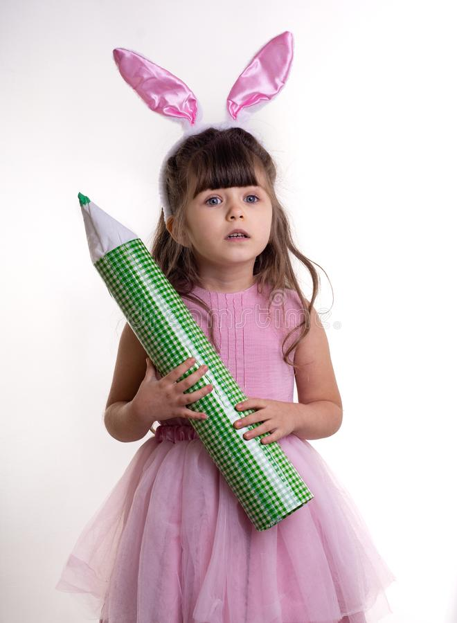 Little girl dressed as the Easter bunny standing on white background and holding pencil royalty free stock photo