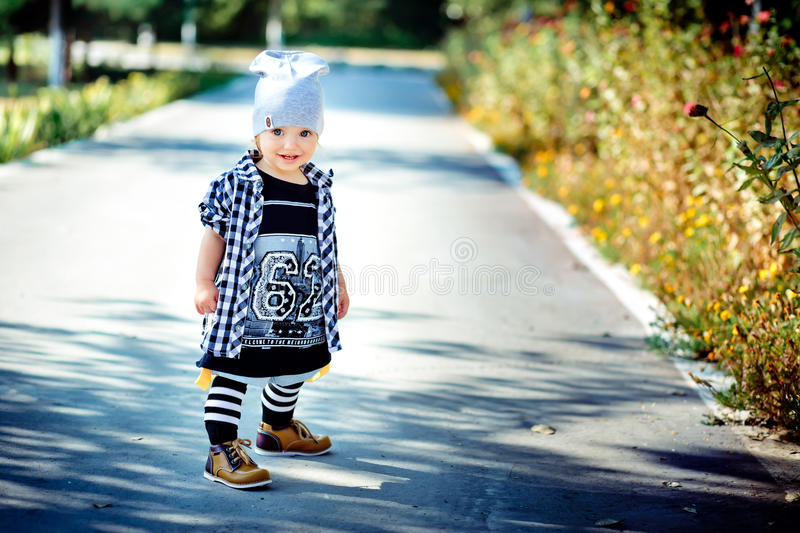 The little girl dressed as the hip-hopper is on a path in park royalty free stock photos