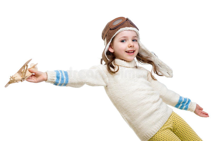 Little girl dressed as pilot playing with wooden airplane stock photography
