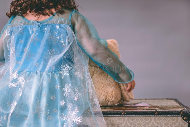 One little girl dressed as a princess holds a teddy bear while sitting on a chest royalty free stock photos
