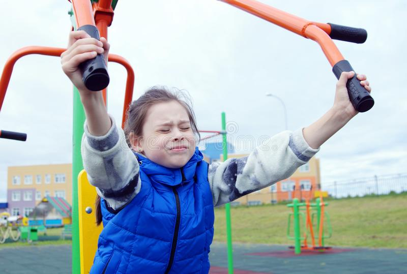 Little girl dressed in blue jeans and sleeveless jacket doing exercises on sports simulators on a sports ground royalty free stock images
