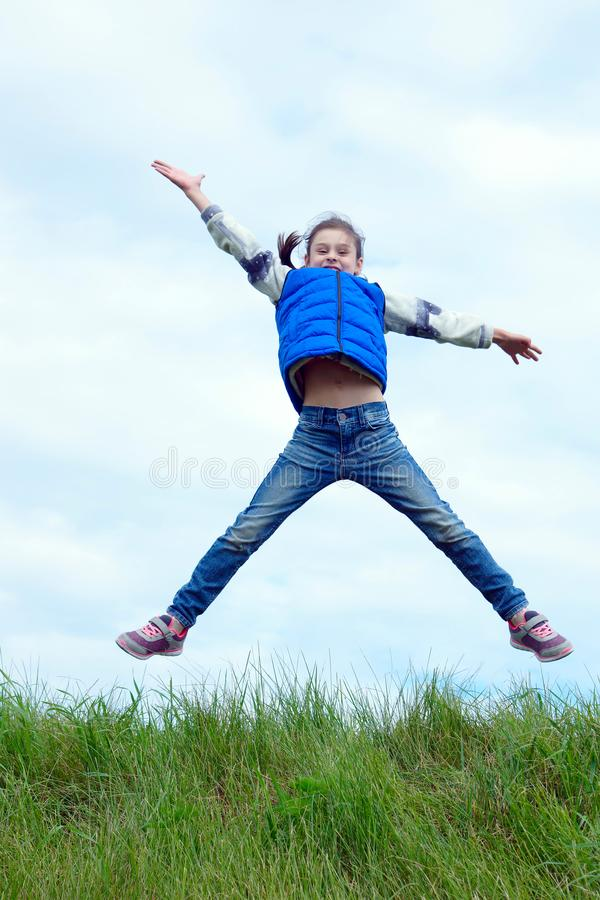 Little girl dressed in blue jeans and sleeveless jacket high jumping over green grass against blue sky royalty free stock photography
