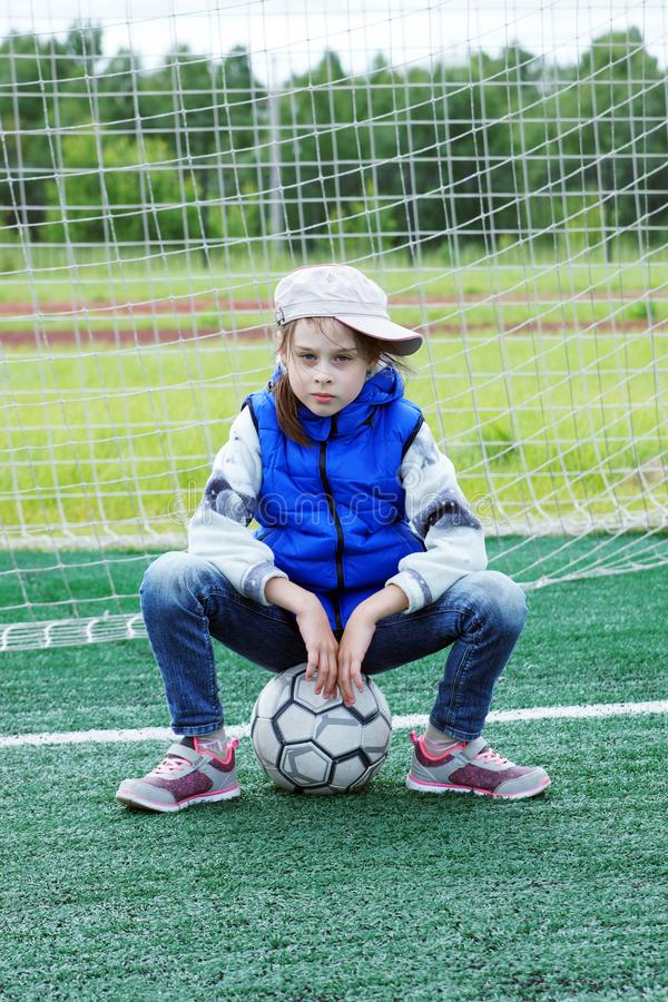 Little girl dressed in blue jeans and sleeveless jacket sitting on the soccer ball near the gate royalty free stock image
