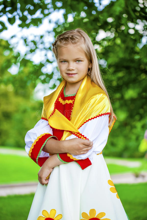 Little girl is dressed in the Russian national dress in summer p. Close up Little girl is dressed in the Russian national dress шт summer park royalty free stock image