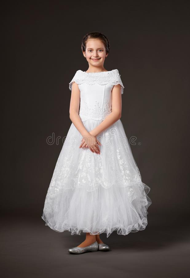 Little girl is dressed in a white ball gown, dark background stock photo